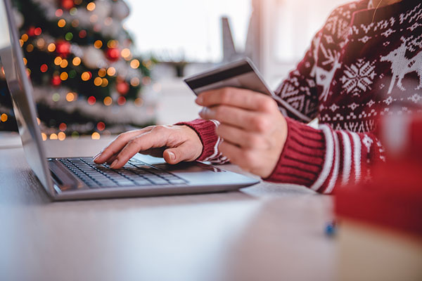 woman doing holiday shopping online on laptop